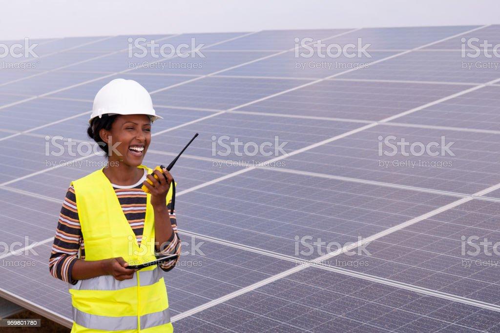 Solar power station worker woman talking on Walkie-Talkie. stock photo