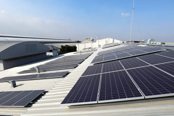 solar pv on industrial roof with exhaust duct chimneys - pannelli solari foto e immagini stock