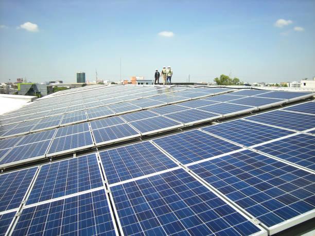 solar pv-dach mit arbeiter zu fuß - sonnenenergiegerät stock-fotos und bilder