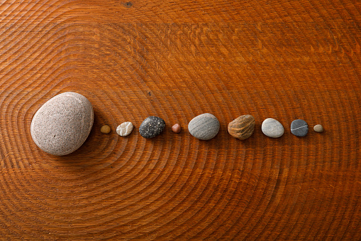 Pebble stones arranged on a wooden floor to a circular orbit