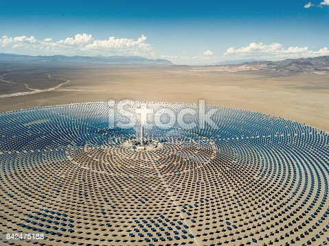 Aerial view from a drone down to large solar thermal power station in the dry desert landscape to the horizon. Nevada, USA.