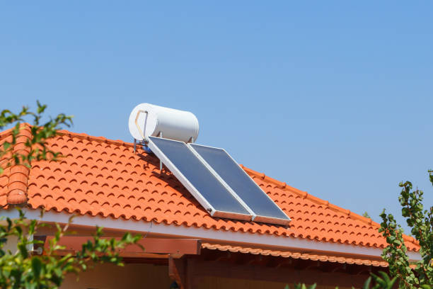 Solar water heating panel and water collector on a house roof. stock photo