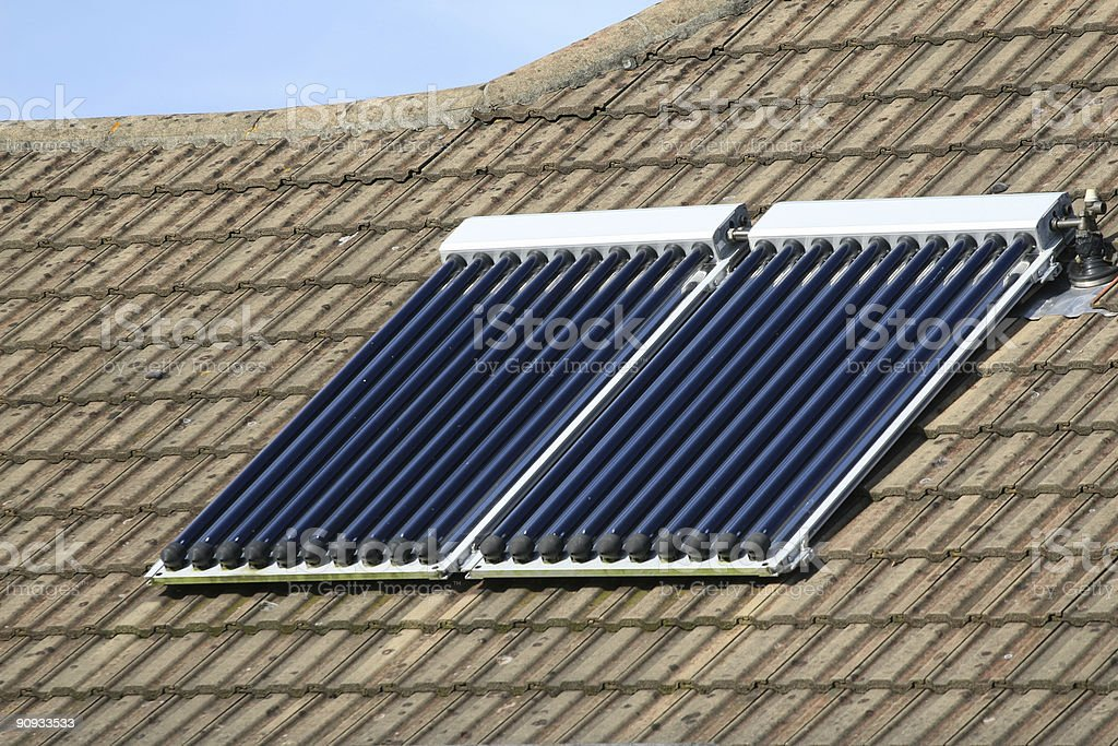 Solar water panel heating on tiled house roof royalty-free stock photo