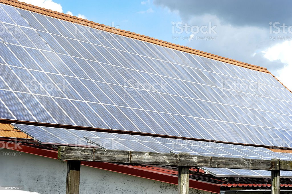 solar-house panels in a row at mixed weather stock photo