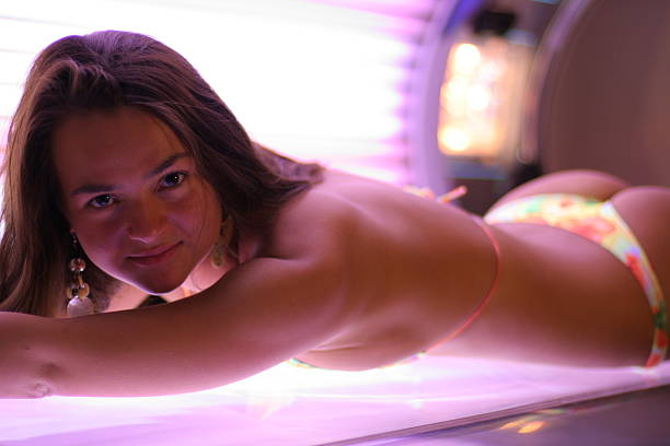 Solarium Girl lays in solarium and try to get some sunlight. Place of action SPA center dark spots face stock pictures, royalty-free photos & images