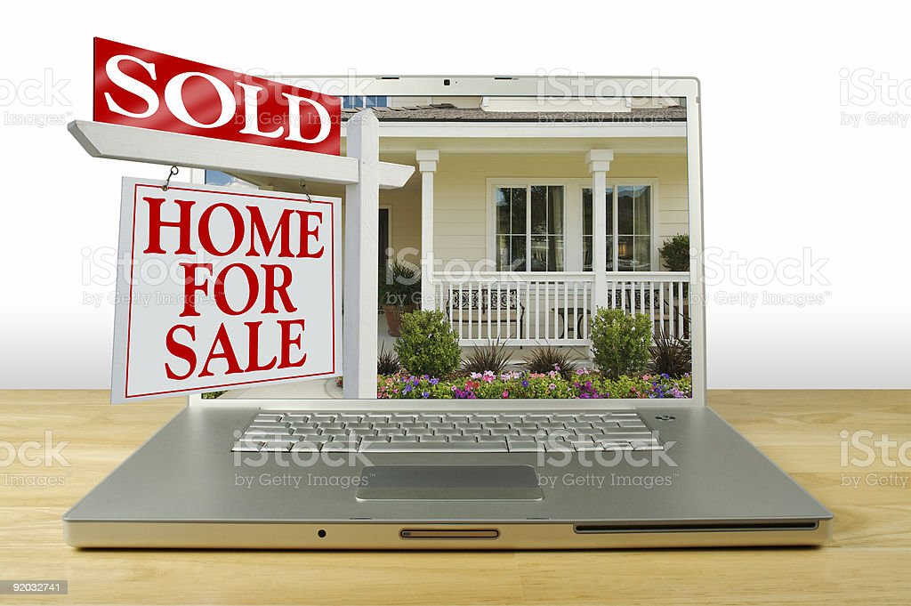 Sold Home for Sale Sign and House on Laptop. stock photo