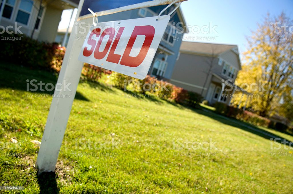 A sold sign in front of a home stock photo