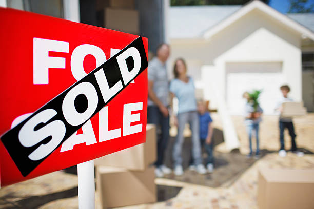 Sold sign on house with family in the background stock photo