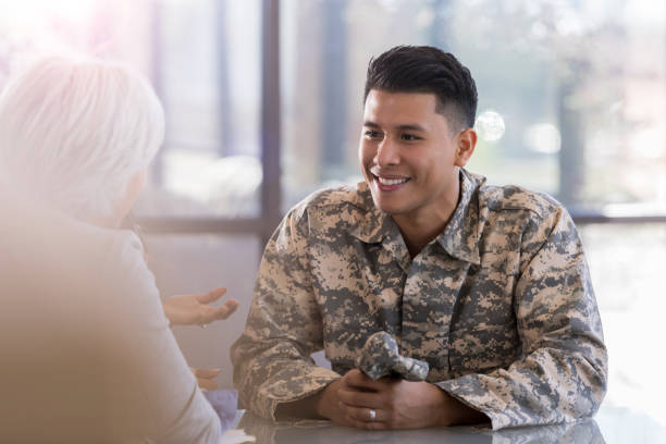 Solder talks with female counselor Cheerful army soldier discusses improvements with his therapist. military lifestyle stock pictures, royalty-free photos & images