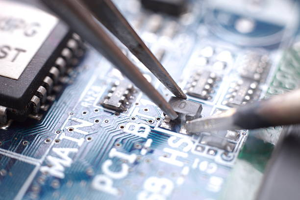 Soldering and assembly of SMD transistor Manual assembly of SMD transistor  (MacroFocus) soldering iron stock pictures, royalty-free photos & images