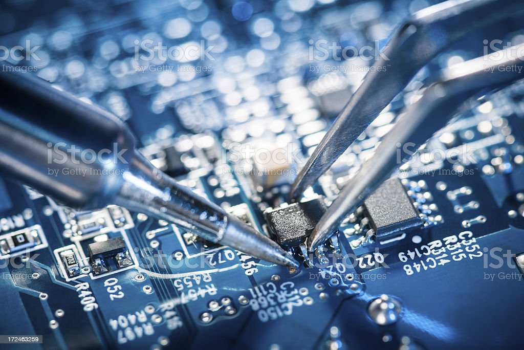 Soldering transistor on circuit board. stock photo
