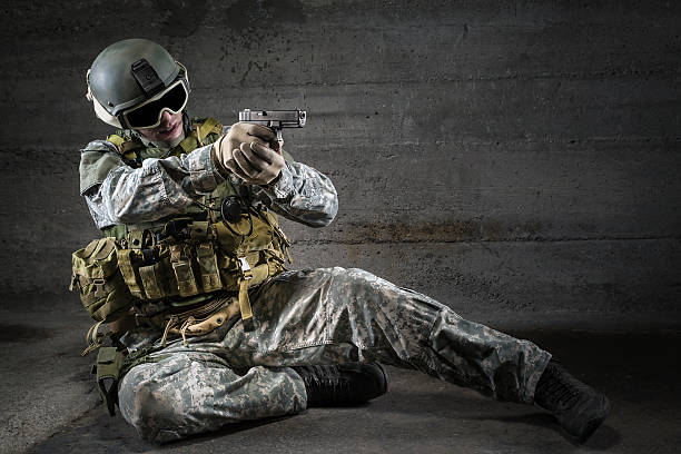 Soldier aiming a pistol stock photo