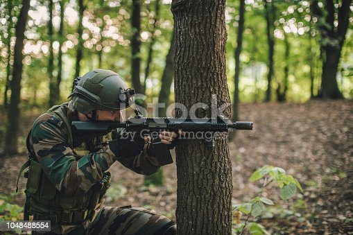 One man soldiers in camouflaged clothing with a gun, deep in wilderness.