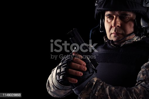 Soldier aiming with black pistol. Image on a dark background.