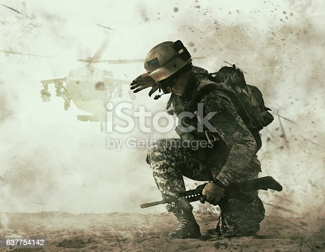 US soldier in the desert during the military operation turning to combat helicopter approaching covering his eyes. Backup is coming