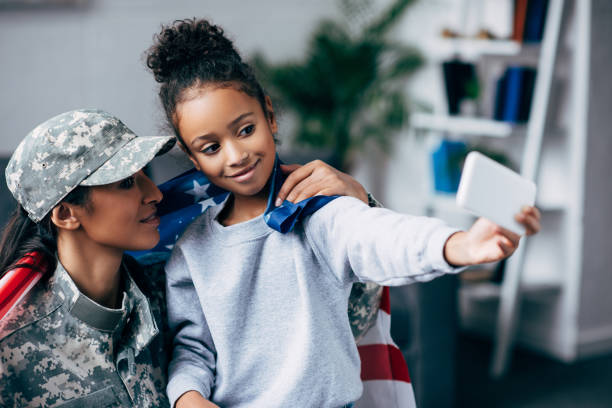soldier and daughter taking selfie stock photo