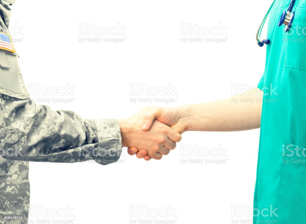 Soldier and doctor shaking hands on white background. Filtered image: cross processed vintage effect. stock photo