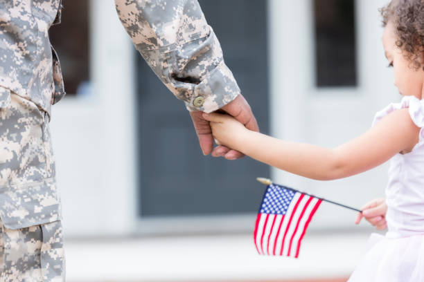 Soldier and his daughter walk hand in hand stock photo