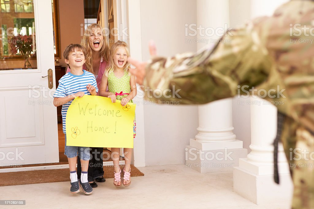 Soldier being greeted by their family as they return home stock photo