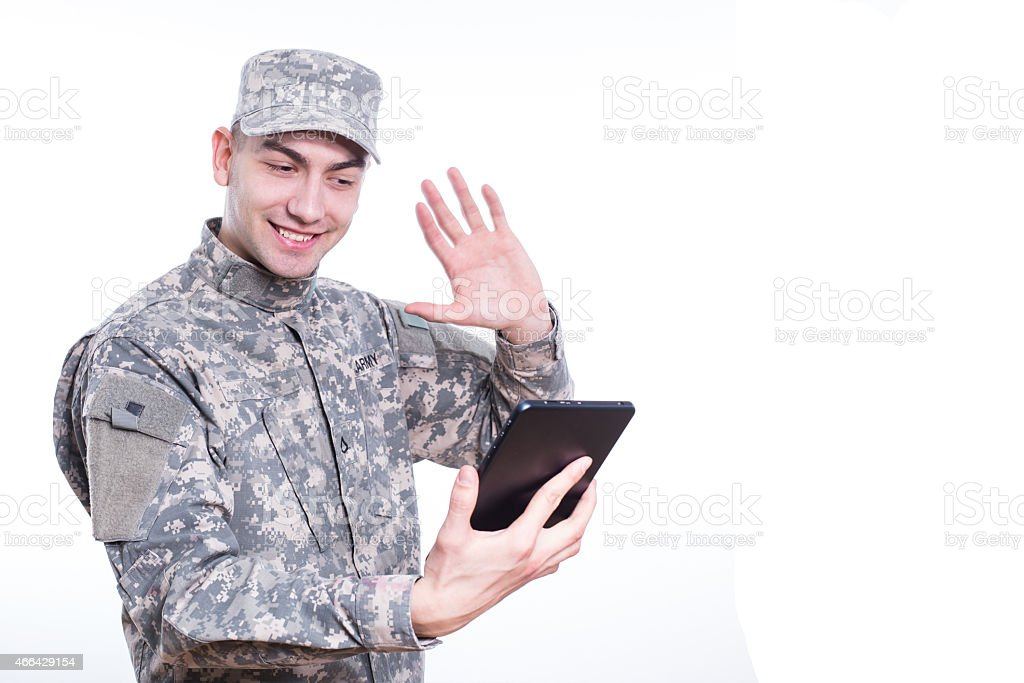 Soldier Calls Home on tablet, Skype stock photo