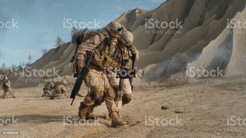 Soldier Carrying Injured One While other Members of Squad Covering Them During Military Operation in the Desert. stock photo