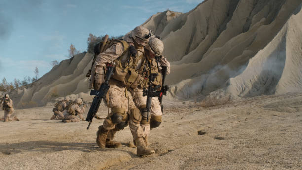 Soldier Carrying Injured One While other Members of Squad Covering Them During Military Operation in the Desert. Soldier Carrying Injured One While other Members of Squad Covering Them During Military Operation in the Desert. advanced tactical fighter stock pictures, royalty-free photos & images
