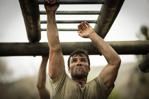 Soldier climbing monkey bars stock photo