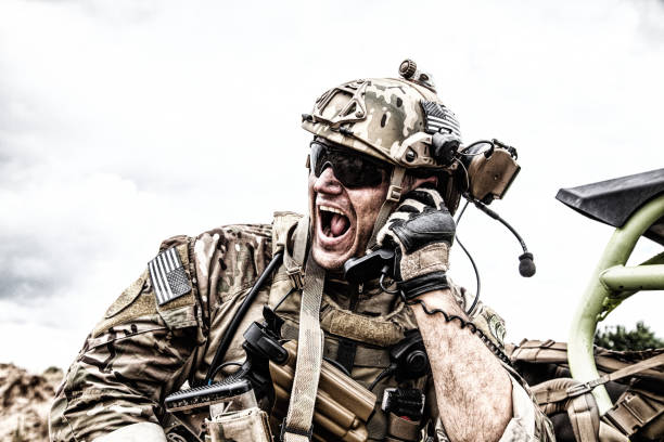 Soldier communicating with command during battle Special forces soldier, military communications operator or maintainer in helmet and glasses, screaming in radio during battle in desert. Calling up reinforcements, reporting situation on battlefield battlefield stock pictures, royalty-free photos & images