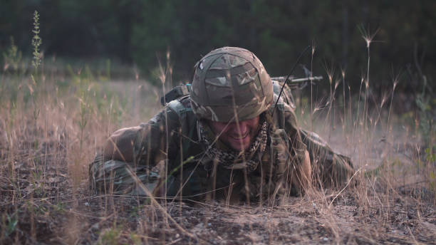 Soldier crawling in field Man in military uniform with gun crawling alone on ground in field. trooper stock pictures, royalty-free photos & images