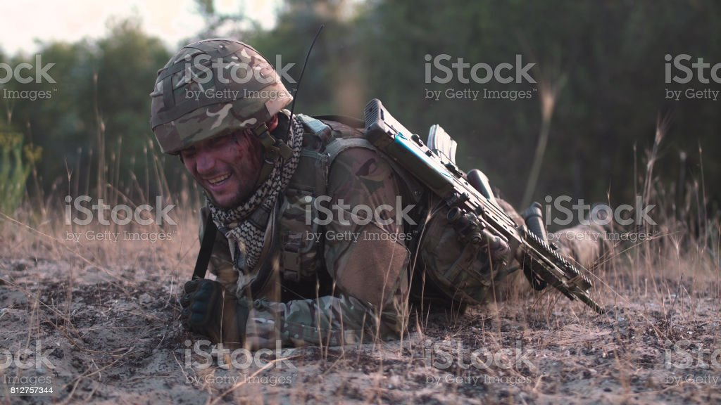 Soldier crawling in field stock photo