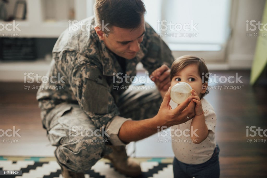 US soldier feeding his baby girl stock photo