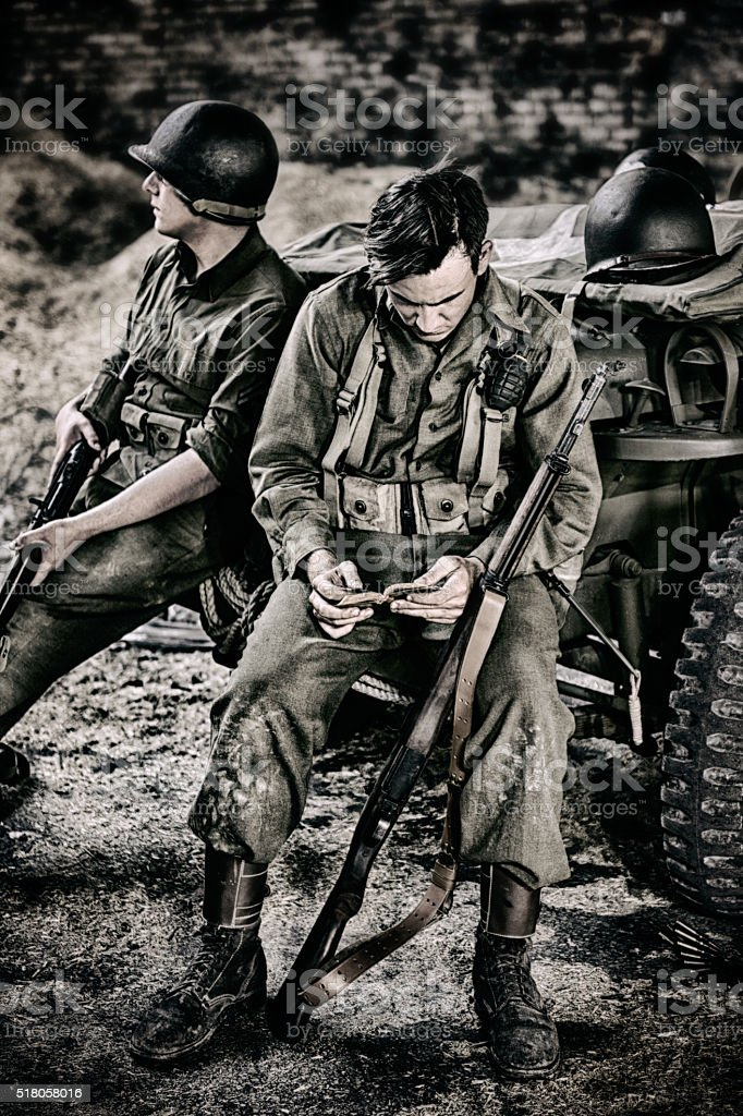 WWII Soldier Finding Comfort Reading His Scriptures stock photo
