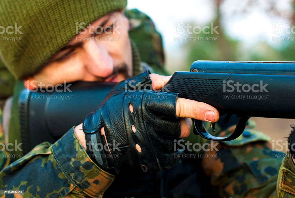 soldier fires his rifle stock photo