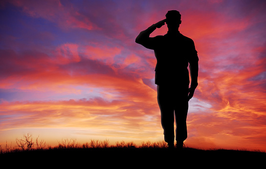 Soldier full body silhouette saluting gesture at sunset copy space