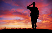 istock Soldier full body silhouette saluting gesture at sunset copy space 1221702998