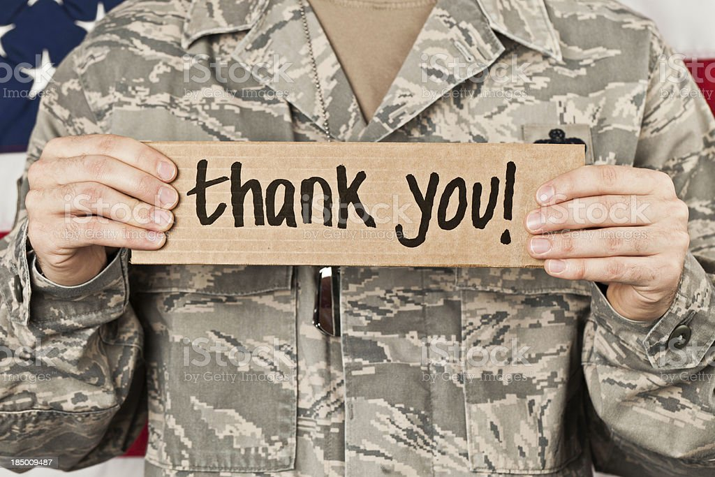 Soldier holding a thank you sign to his chest stock photo