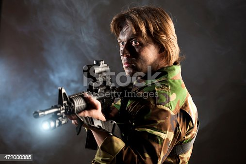soldier holding a weapon with searchlight in smoke
