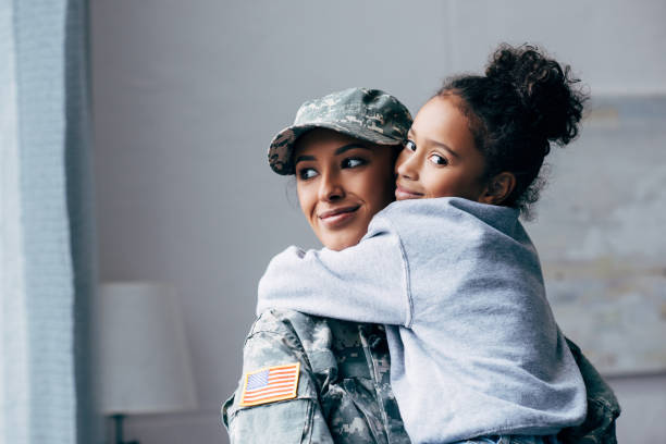 soldier holding daughter on arms smiling african american soldier in military uniform holding daughter on arms at home 2012 stock pictures, royalty-free photos & images