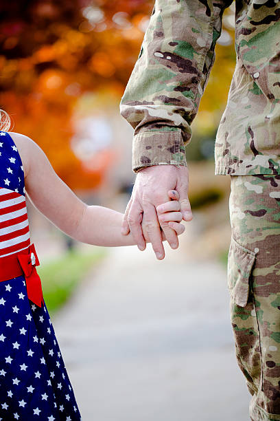 Soldier holding daughter's hand stock photo
