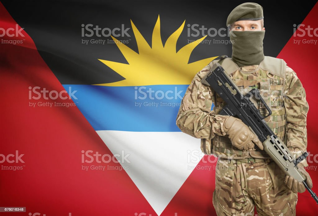 Soldier holding machine gun with flag on background series - Antigua and Barbuda stock photo