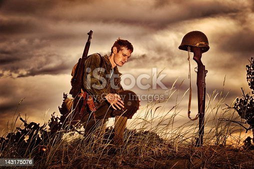 Soldier in full combat uniform kneeling At the marked, temporary grave of another soldier.  Gun stuck in ground with bayonet.  Helmet gun, bayonet and strap clearly visible in ominous sky.