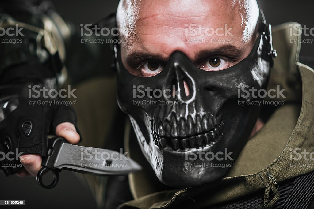 soldier in a black mask on a dark background. stock photo