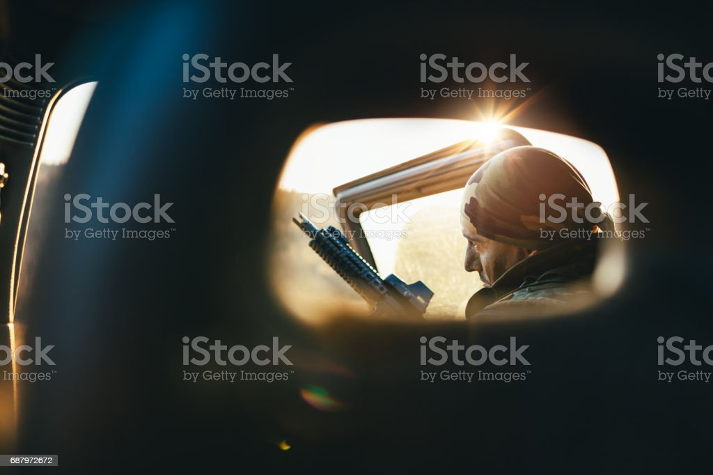 Soldier in back of vehicle stock photo