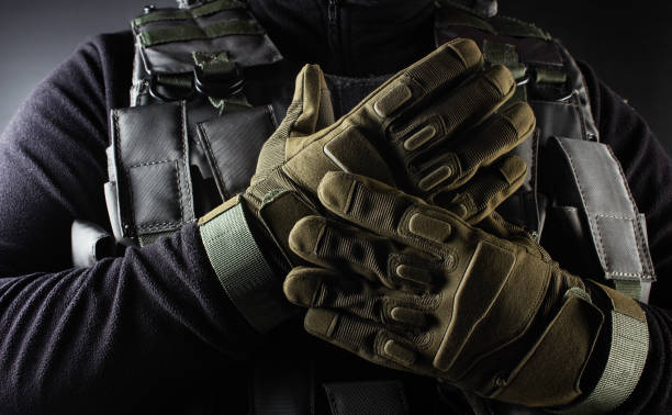 Soldier in black armor tactical vest and gloves standing. Photo of a fully equipped soldier in black armor tactical vest and gloves standing on black background closeup front view. trooper stock pictures, royalty-free photos & images