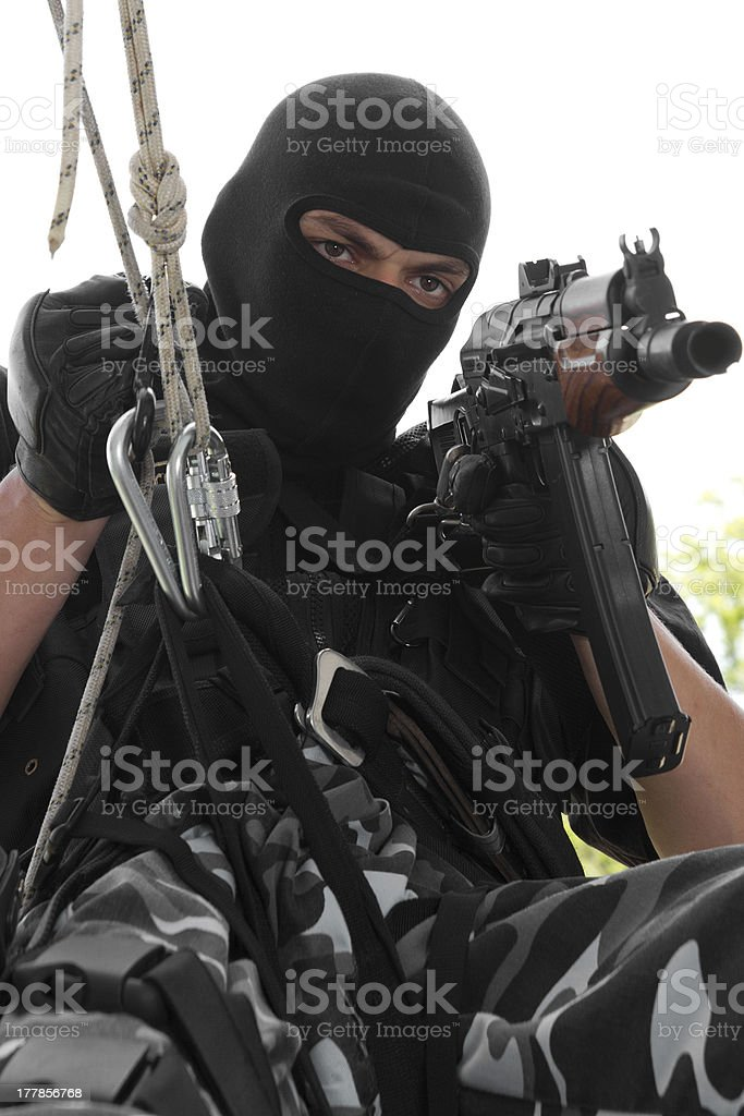 Soldier in black mask hanging on rope with Ak-47 rifle stock photo