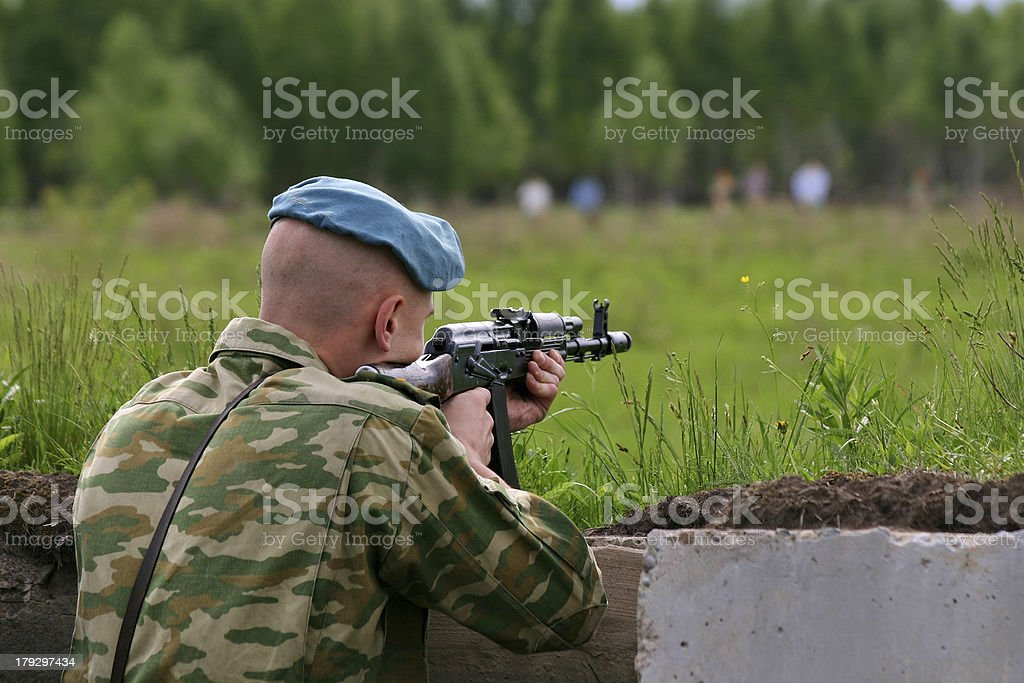 soldier in camouflage uniform with Kalashnikov is shooting royalty-free stock photo