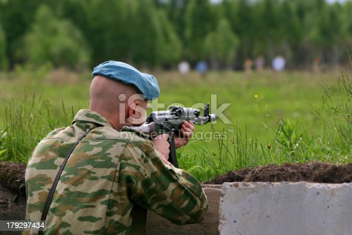 istock soldier in camouflage uniform with Kalashnikov is shooting 179297434