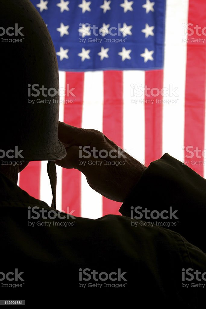 Soldier in field dress saluting American flag royalty-free stock photo