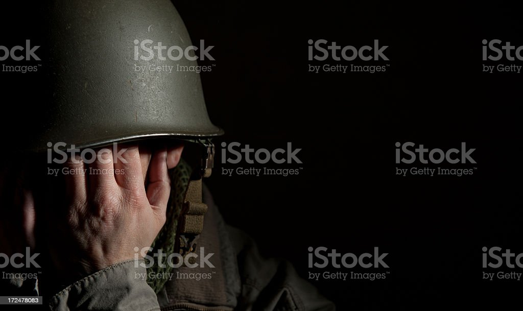 Soldier in his helmet with hands covering face stock photo