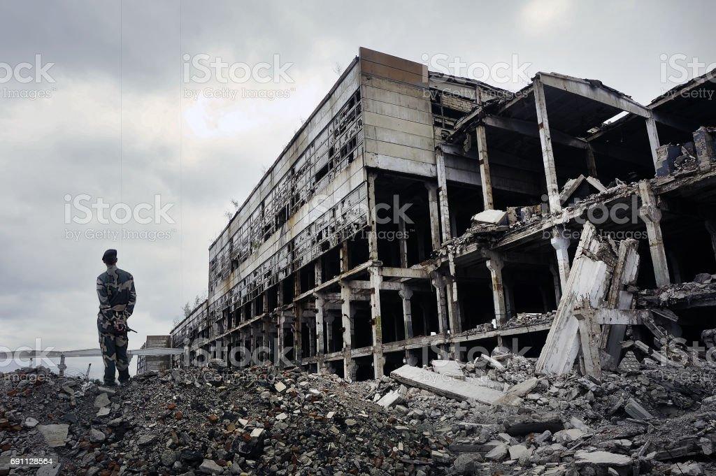 Soldier in military uniform stands on the ruins stock photo